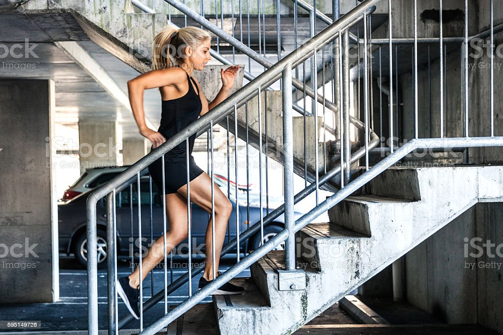 Woman exercising running up on stairs stock photo
