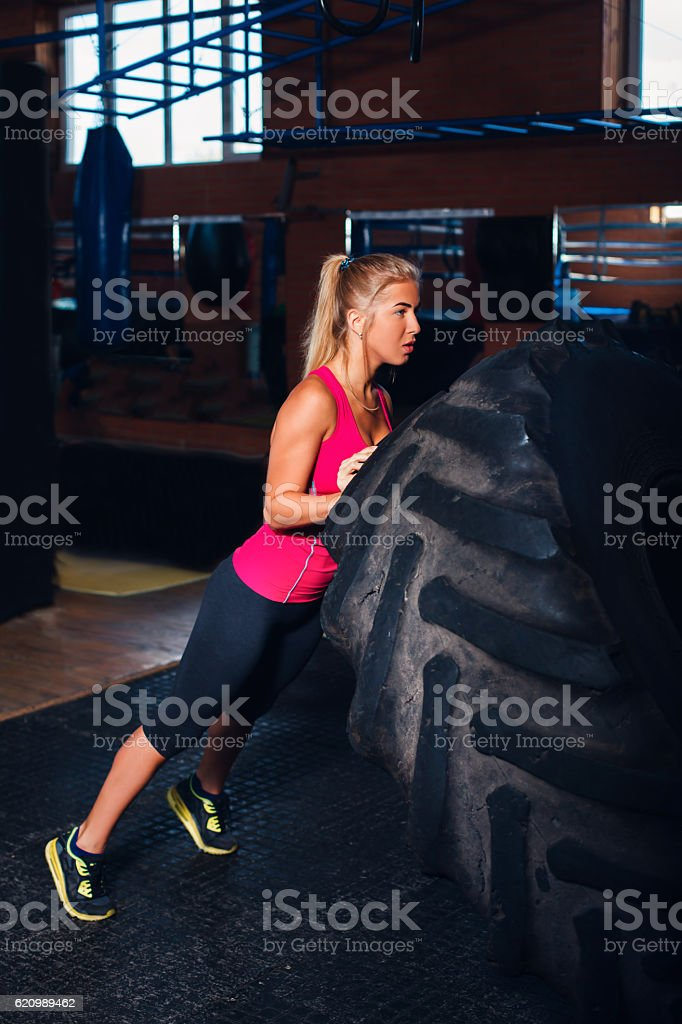 Woman exercising with a big tire stock photo