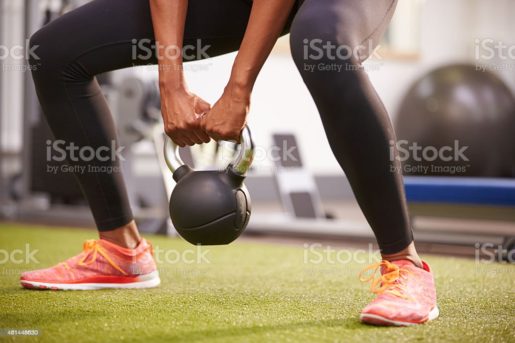 Woman exercising with a kettlebell weight, low-section crop stock photo
