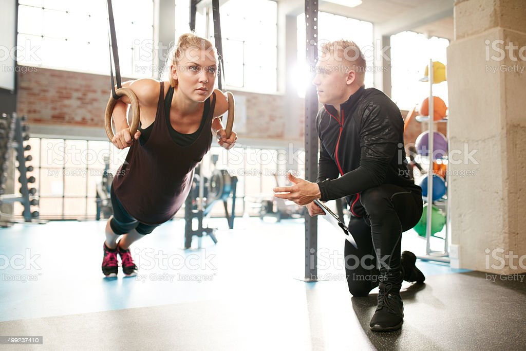 Woman exercising with a trainer at the gym stock photo