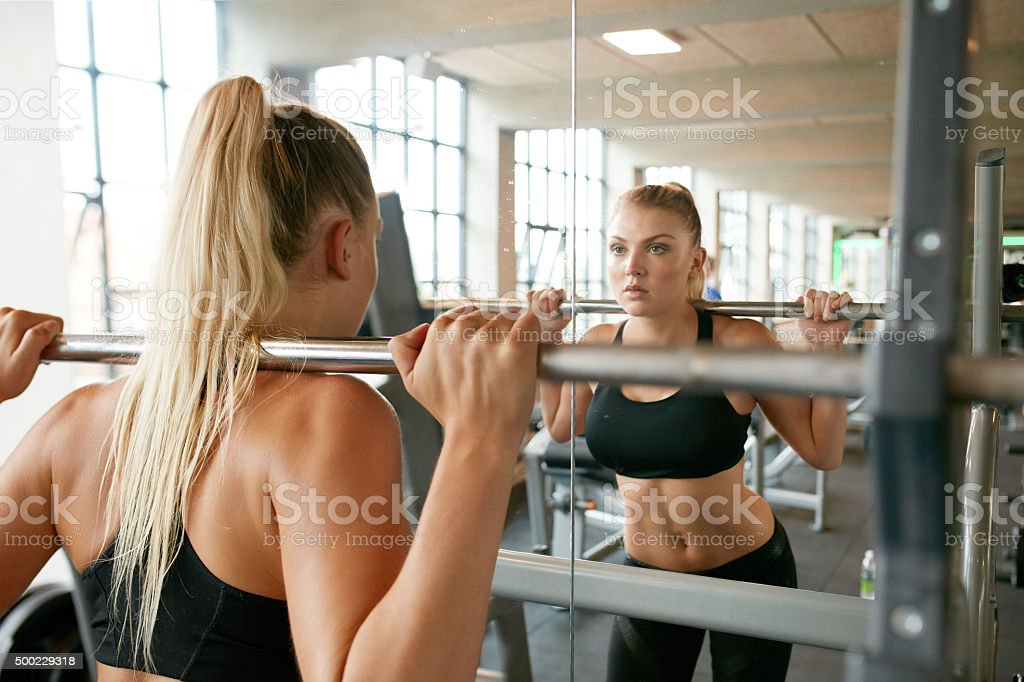 Woman exercising with barbell in gym stock photo