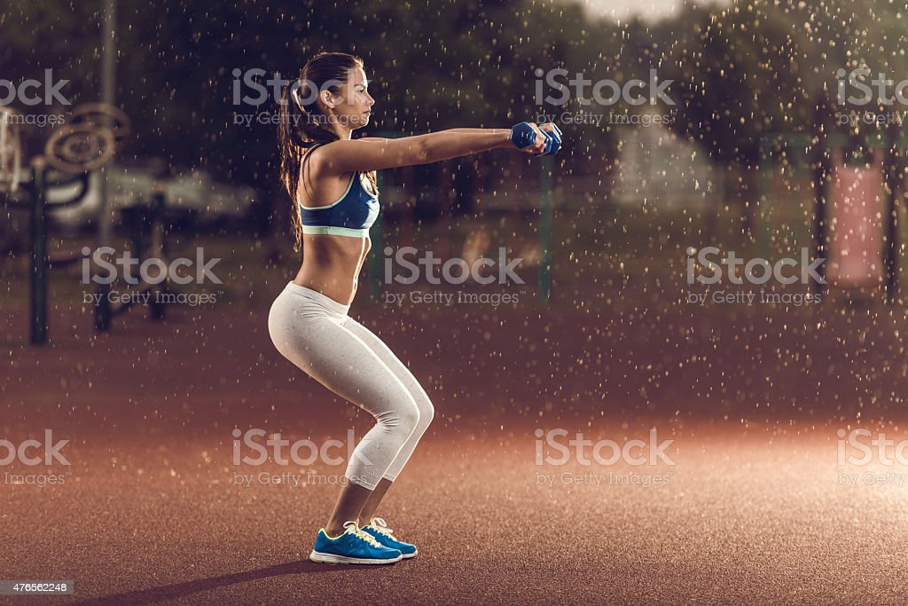 Woman exercising with dumbbells in squat position on rainy day. stock photo