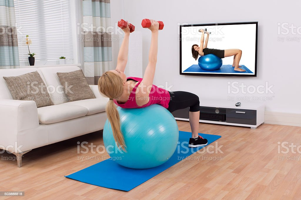 Woman Exercising With Fitness Ball And Dumbbell stock photo