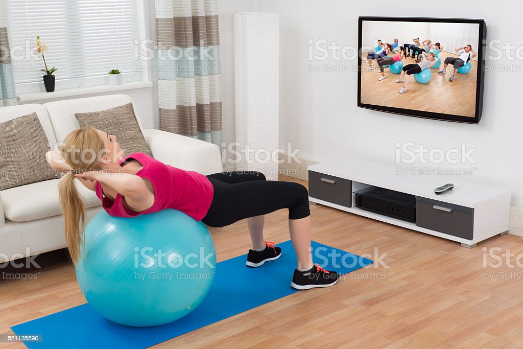Woman Exercising With Fitness Ball While Watching Program stock photo