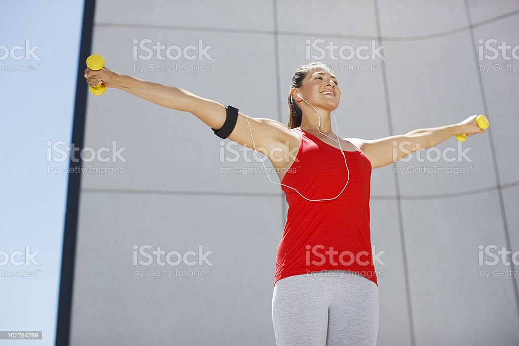 Woman exercising with hand weights outdoors royalty-free stock photo