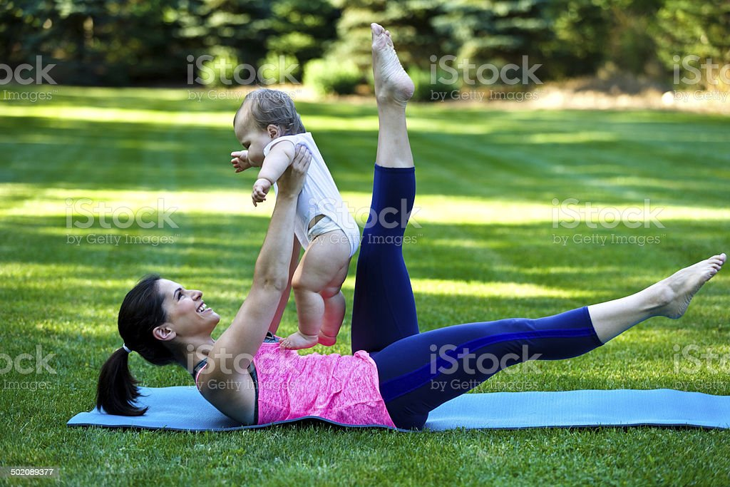 Woman exercising with her baby boy stock photo