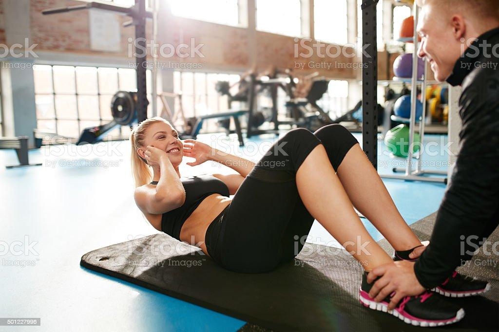 Woman exercising with her personal trainer in the gym stock photo