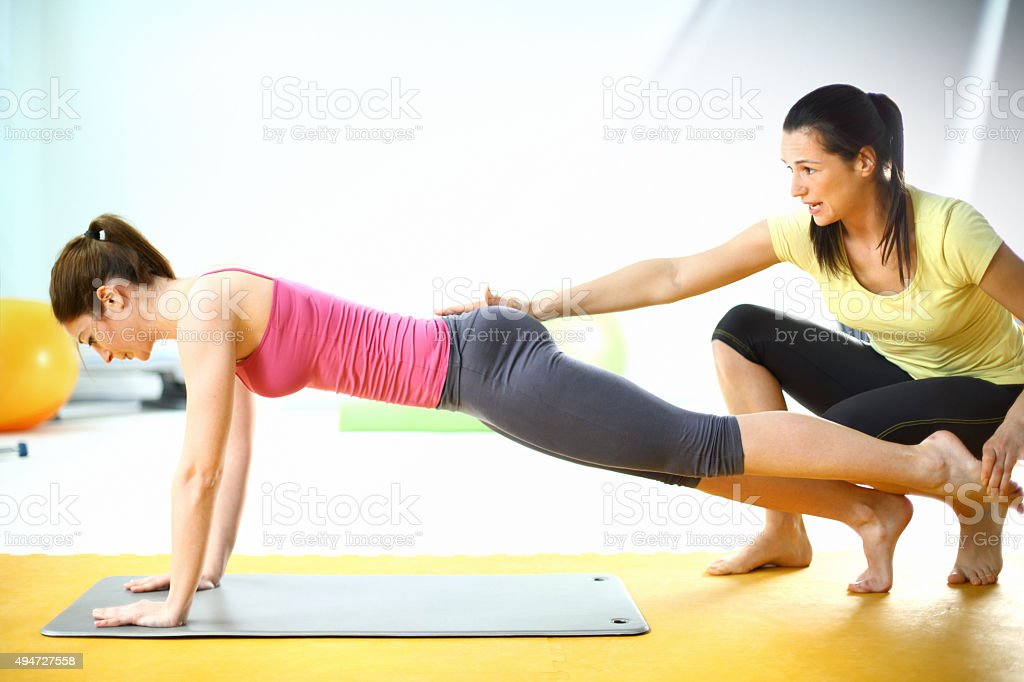 Woman exercising with instructor. stock photo