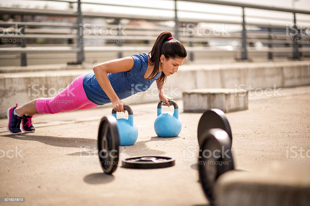 Woman exercising with kettlebells stock photo