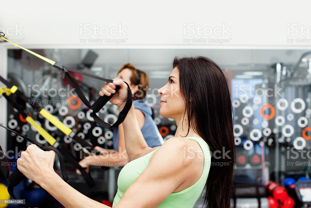 Woman Exercising with Suspension Straps stock photo