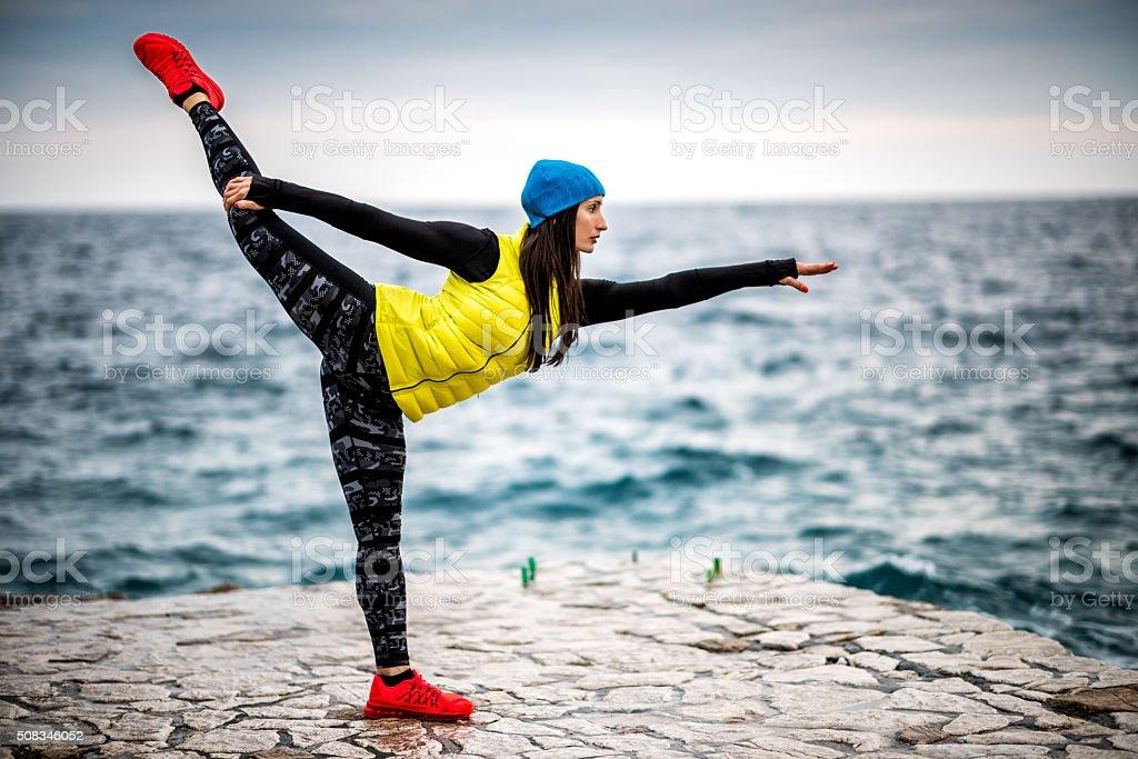 Woman exercising yoga near the sea stock photo