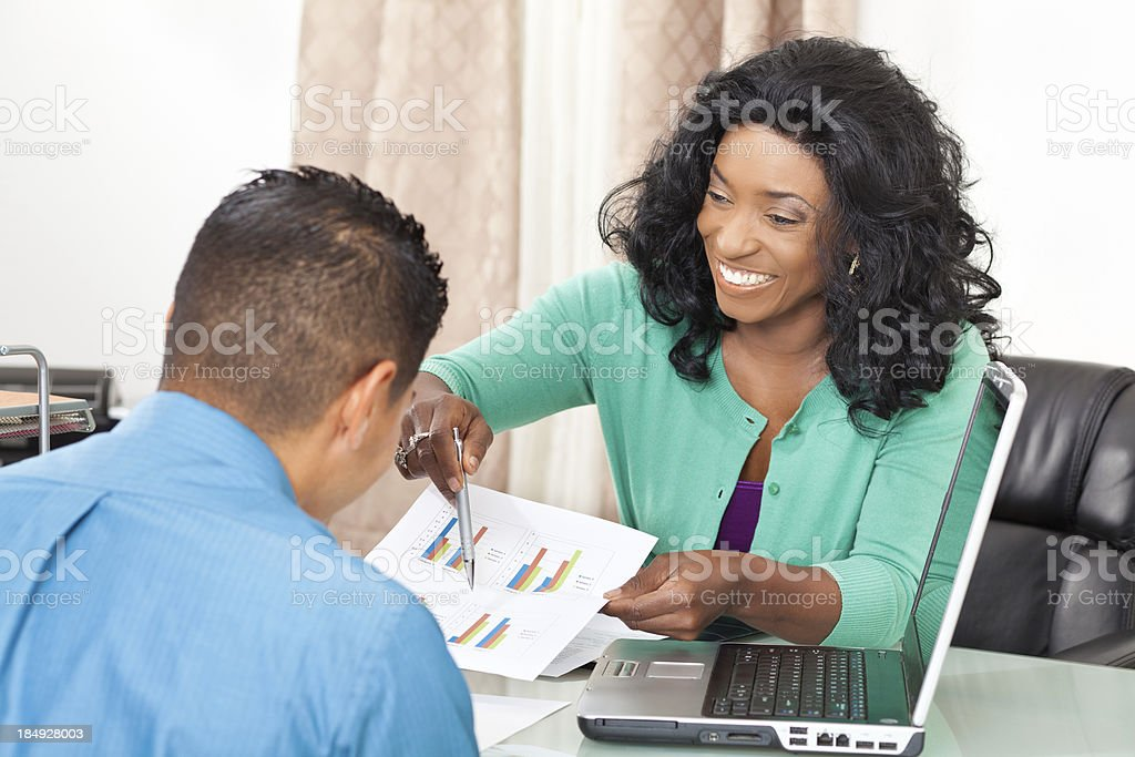 Woman explaining financial chart figures to client royalty-free stock photo