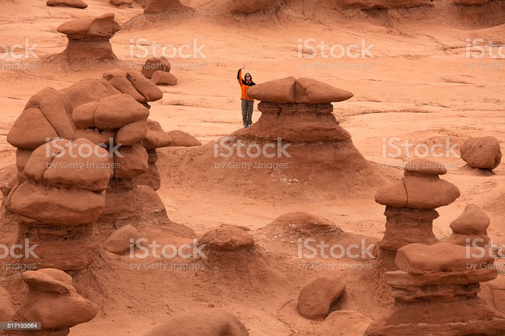 Woman explores giant stone mushrooms Utah's Goblin Valley State Park stock photo