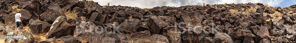 Woman Exploring Hillside of Petroglyphs Panorama stock photo
