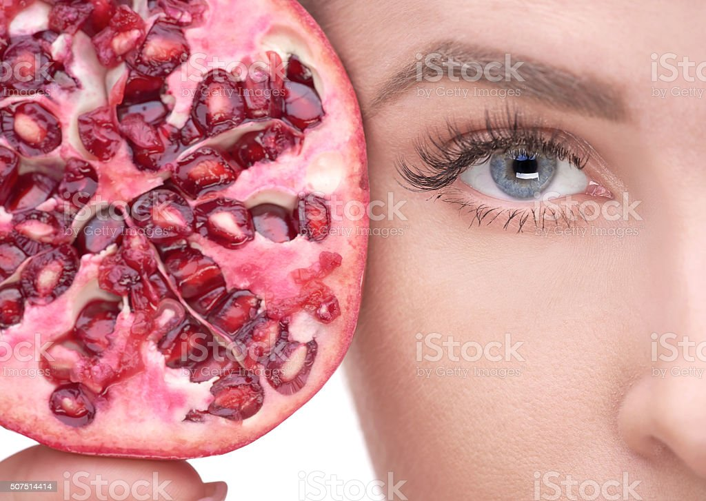woman eye near pomegranate stock photo