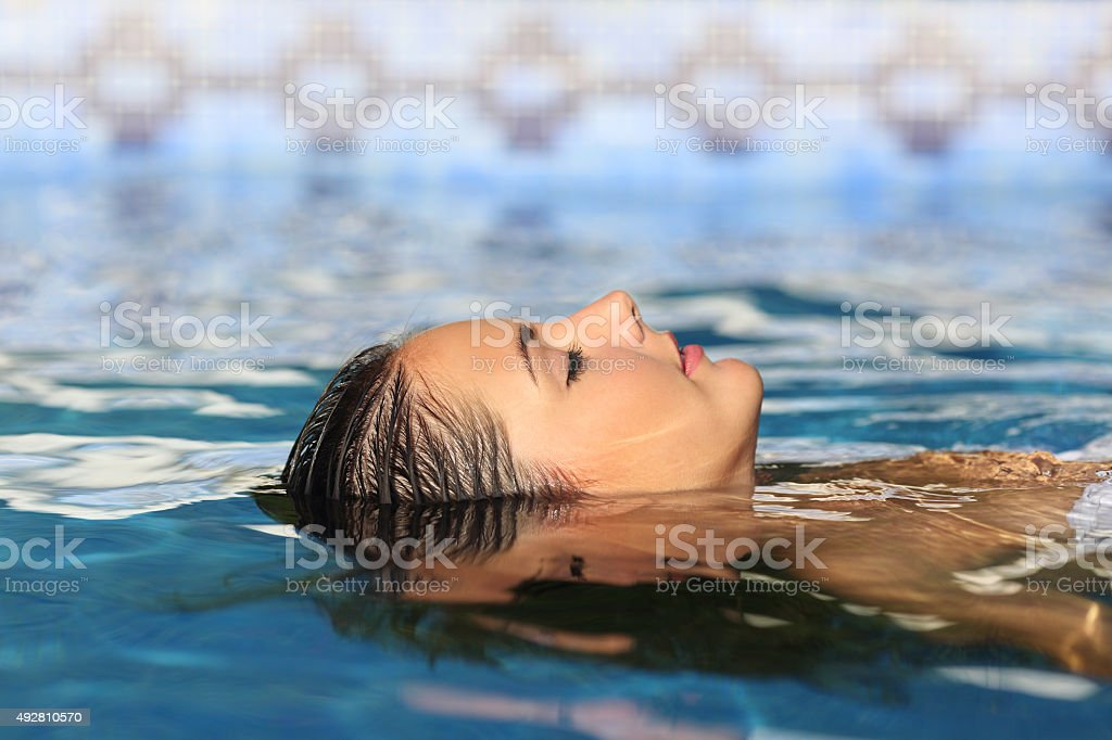 Woman face relaxing floating on water of pool or spa stock photo