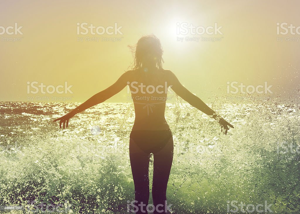 Woman facing the sun with waves crashing at her feet stock photo