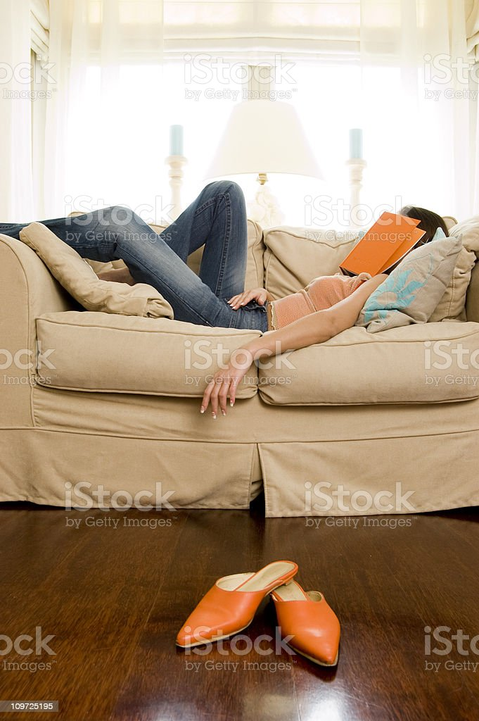 Woman Fallen Asleep with Book on couch royalty-free stock photo