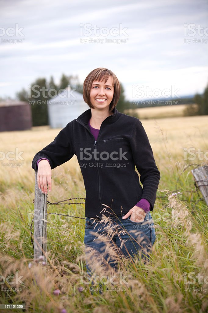 A woman farmer standing in the middle of a grassy field stock photo