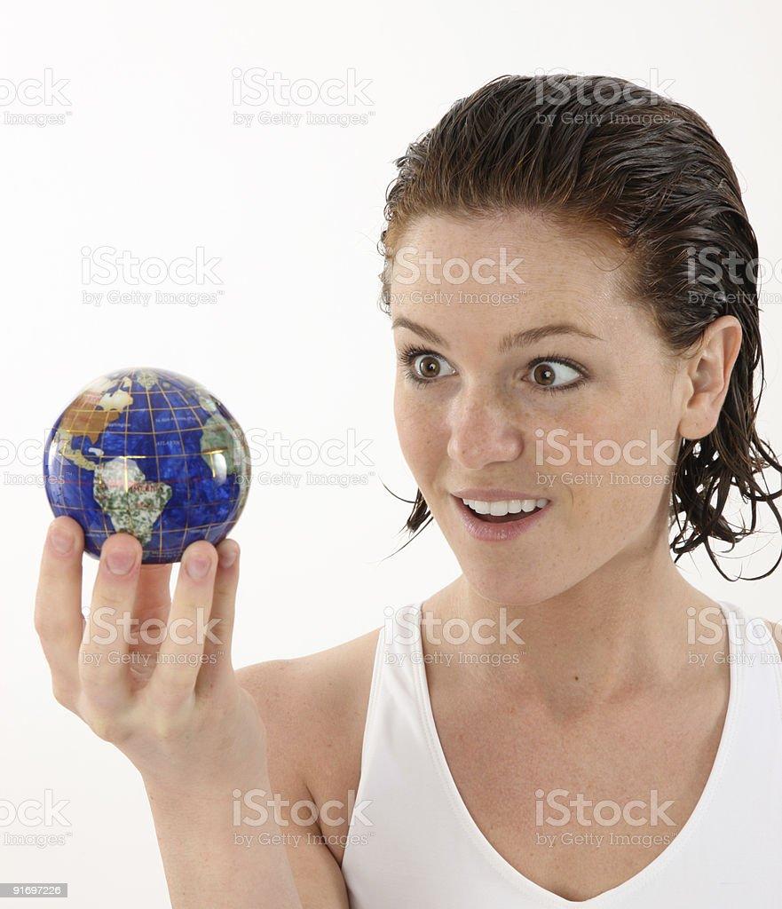 Woman fascinated looking at a globe royalty-free stock photo