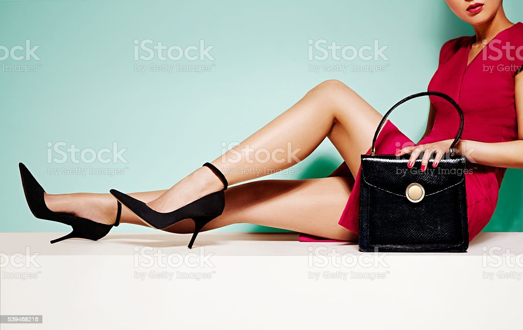 Woman fashion with black purse hand bag with high heels shoes. stock photo