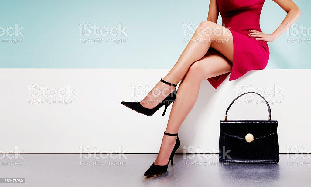 Woman fashion with black purse handbag with high heels shoes. stock photo