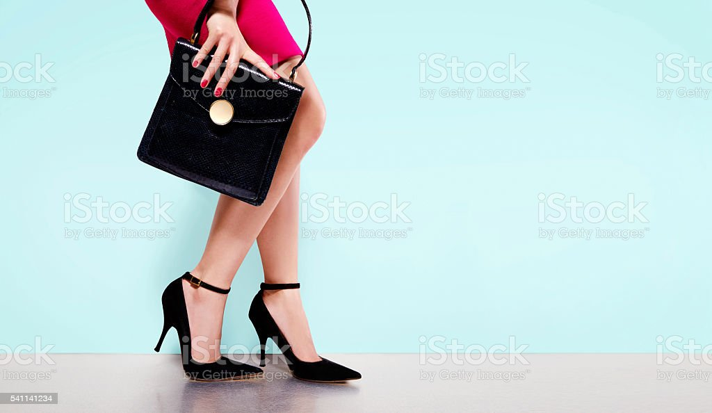 Woman fashion.black purse hand bag with high heels shoes. stock photo