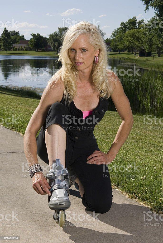 Woman fastening her roller skates stock photo