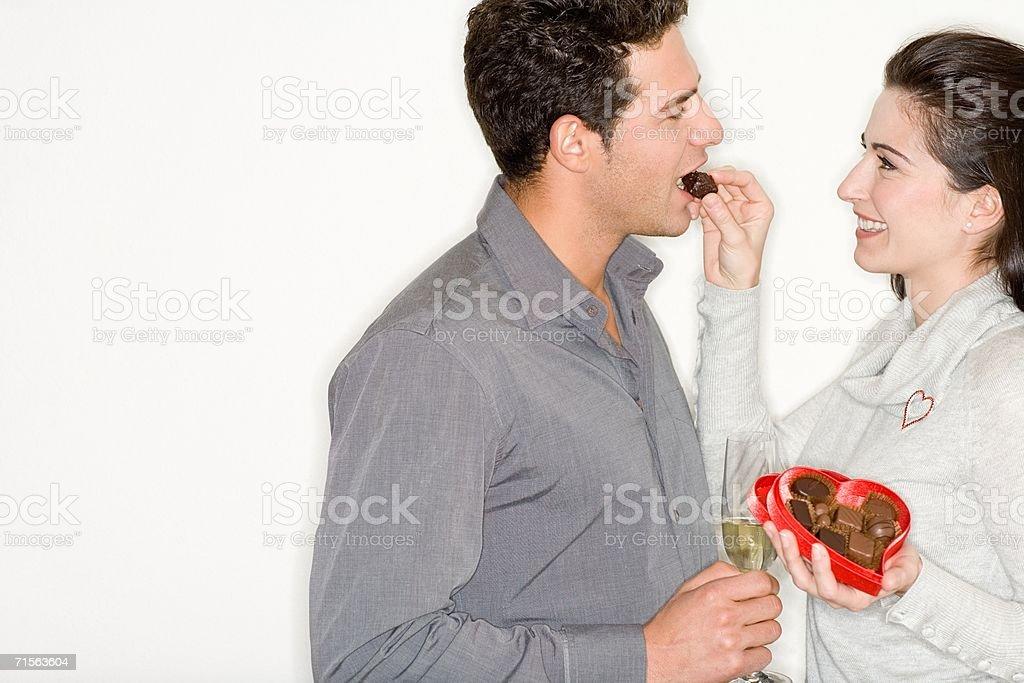 Woman feeding chocolates to boyfriend stock photo