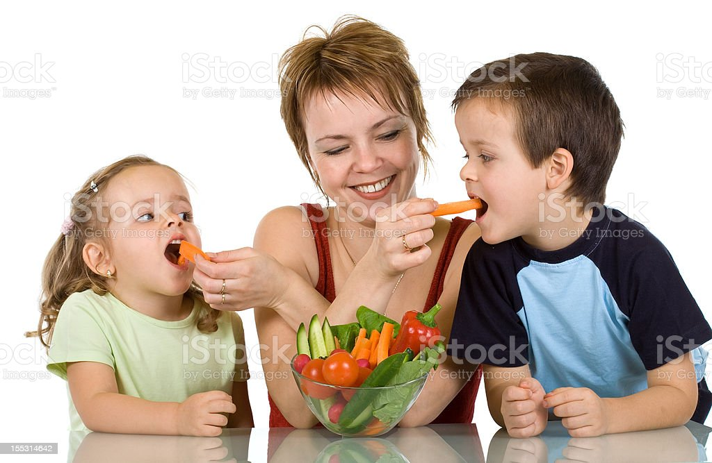 Woman feeding kids with vegetables royalty-free stock photo