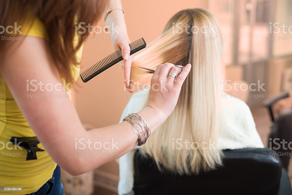 woman feel relaxes when stylist is cuting her hair stock photo