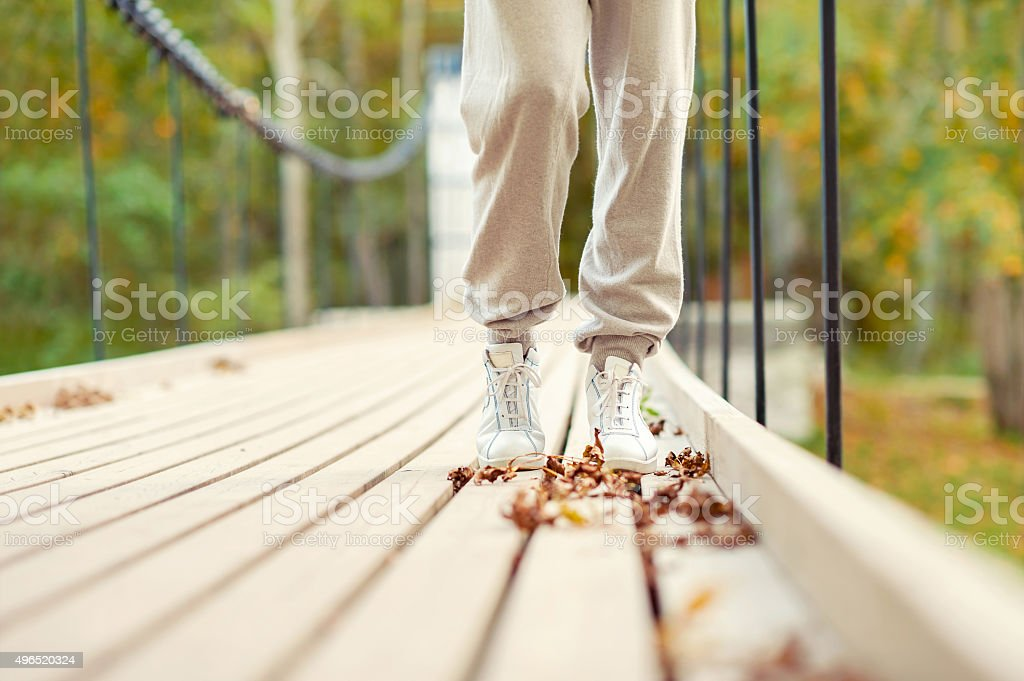 Woman feet in white shoes walking in autumn park stock photo