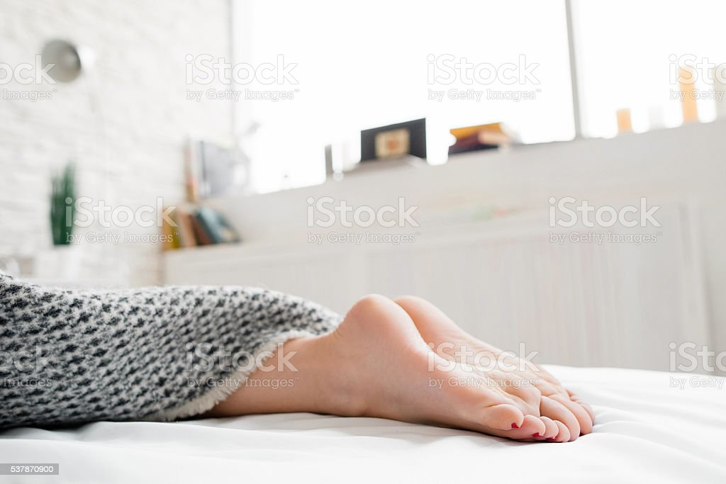 Woman feet on bed under blanket stock photo