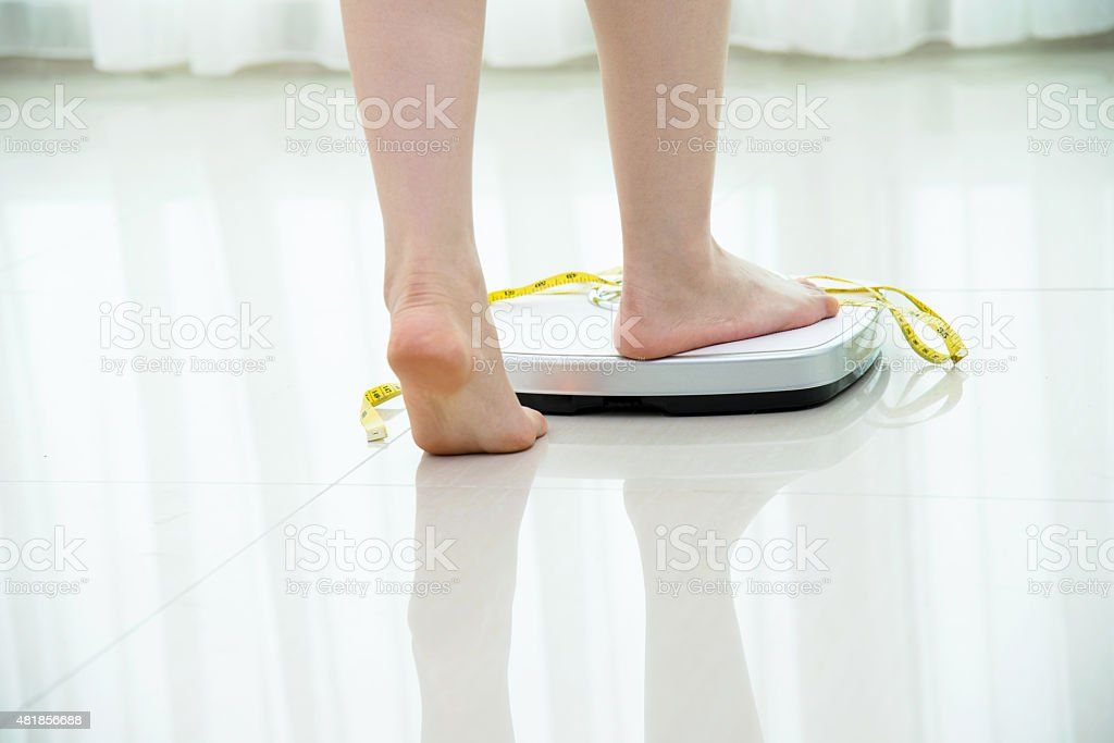 Woman feet on scale stock photo