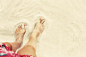 Woman feet on sea beach sand. Happy summer vacation
