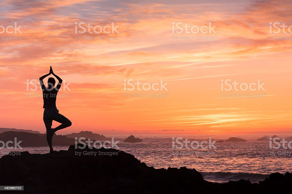 Woman fighting anxiety with yoga near the sea stock photo