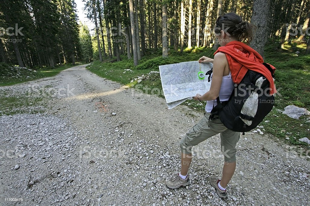 A woman figuring out where to go on her map in the woods stock photo