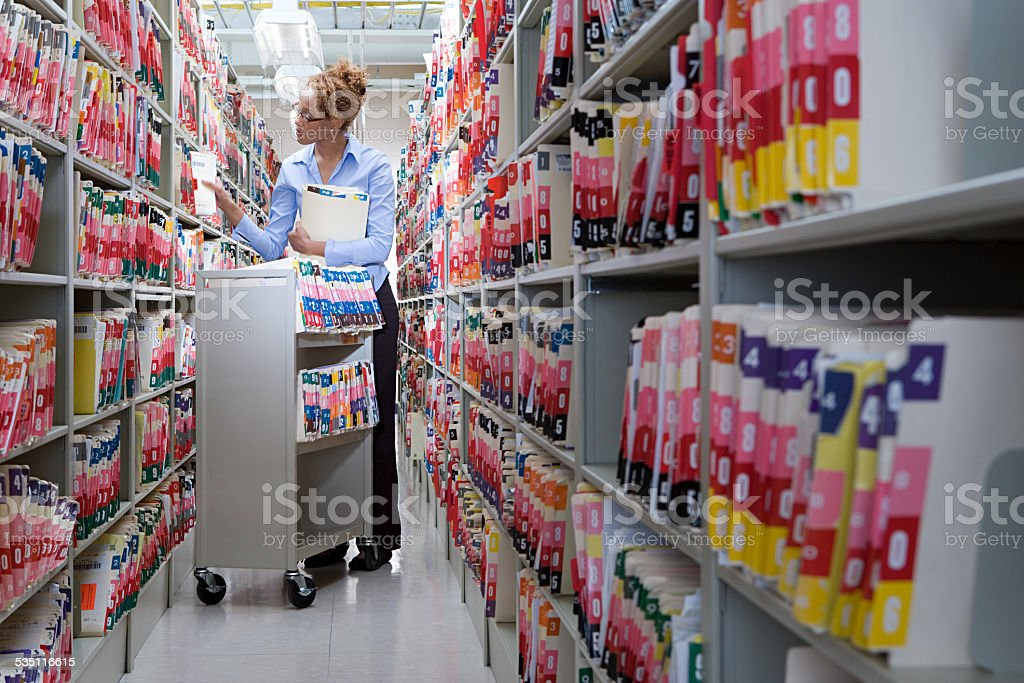Woman filing in hospital archives stock photo
