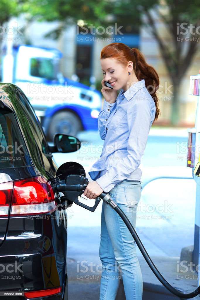 woman filling compact car tank with petrol at gas station stock photo