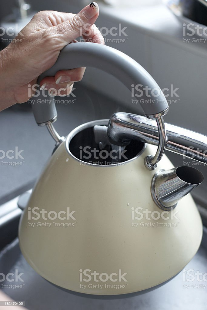 Woman filling kettle with tap water royalty-free stock photo