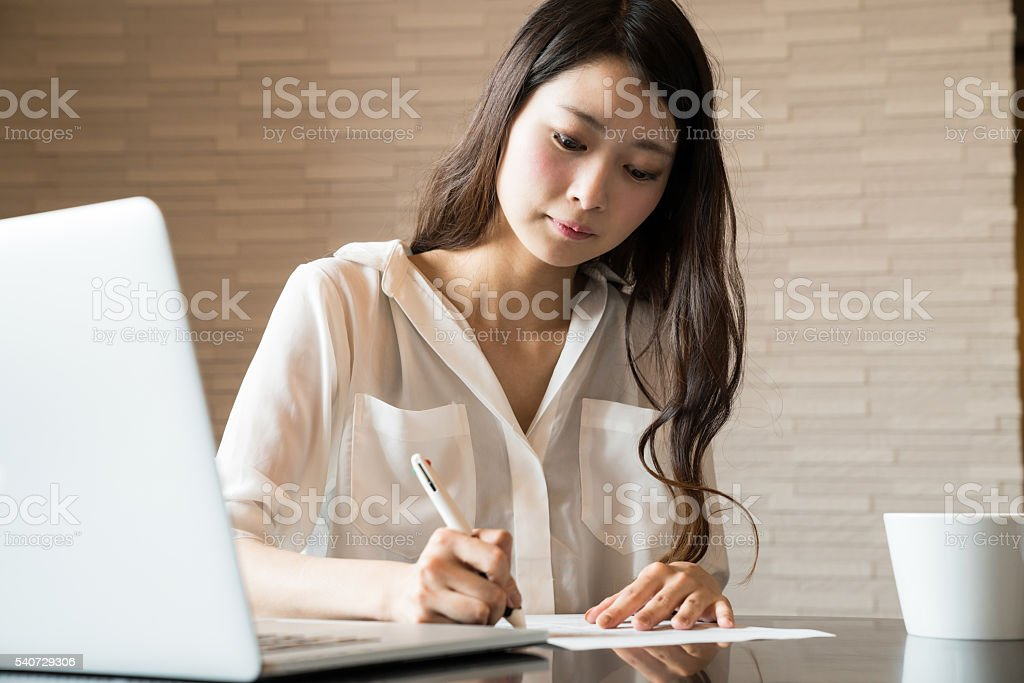 Woman filling out important paper documents stock photo