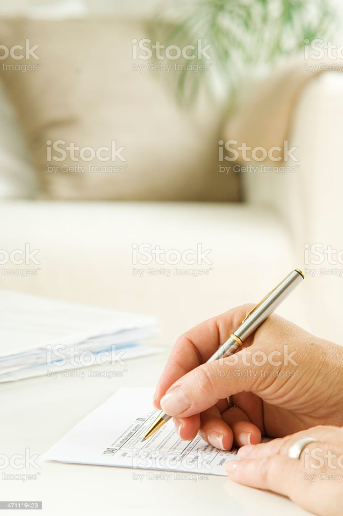Woman filling the tax form stock photo