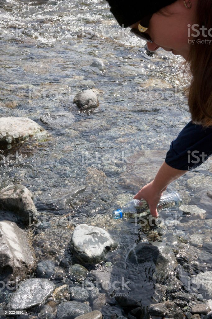 Woman filling water bottle in Fiordland National Park, New Zealand stock photo