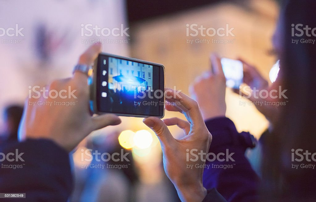 Woman filming a concert with smart phone stock photo