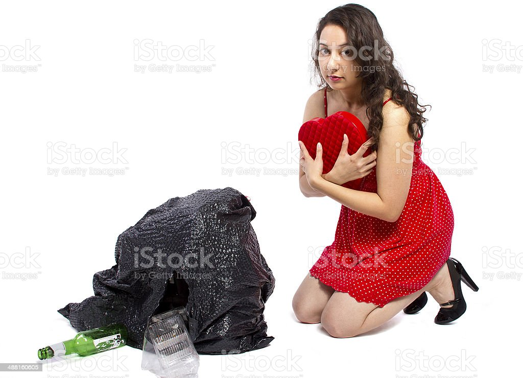 Woman Finding a Heart Gift Thrown Away In The Trash stock photo