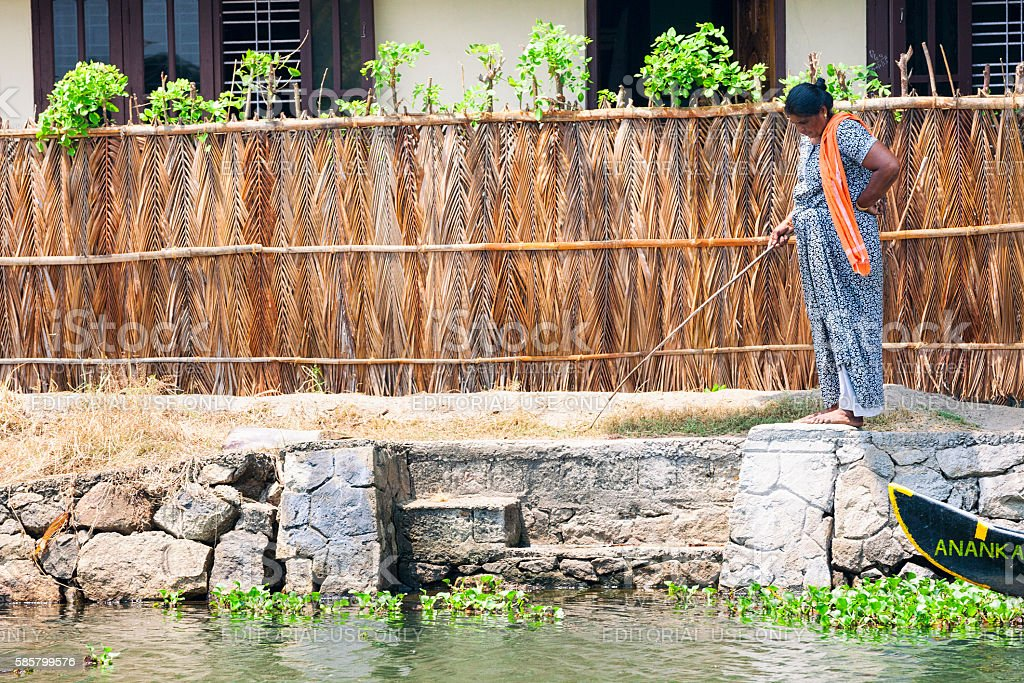 Woman fishing along the Kerala Backwaters in India stock photo