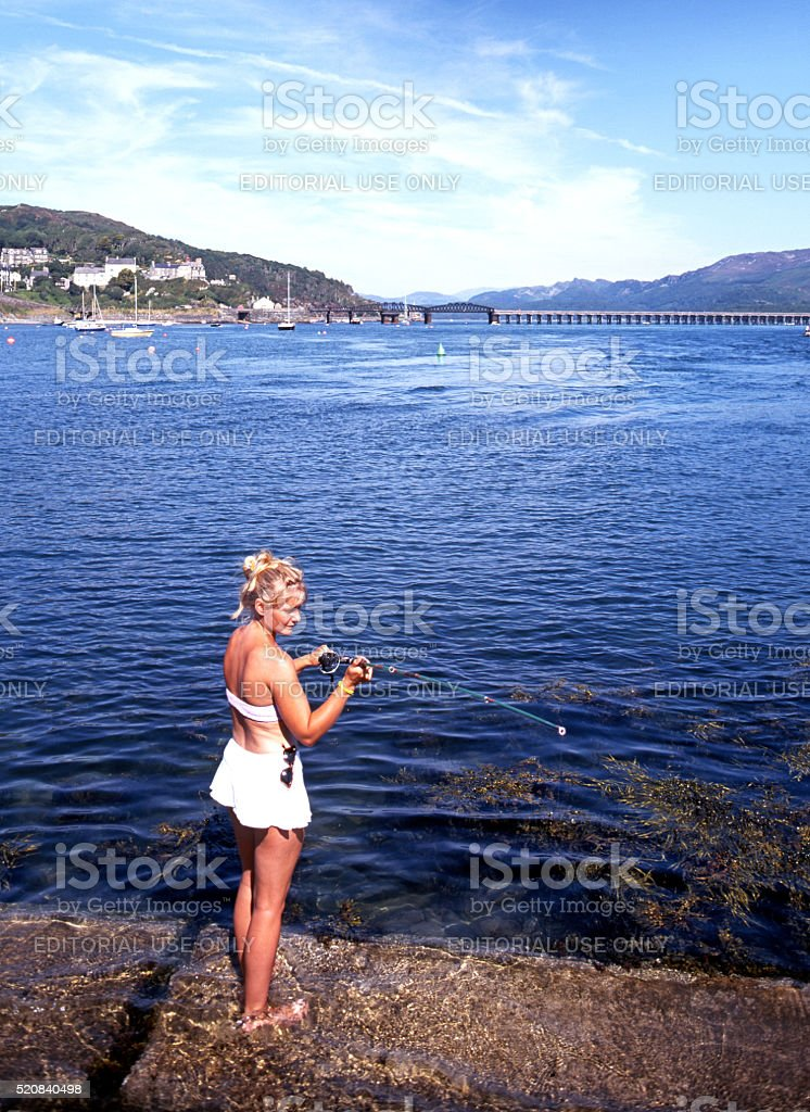 Woman fishing in Barmouth harbour. stock photo