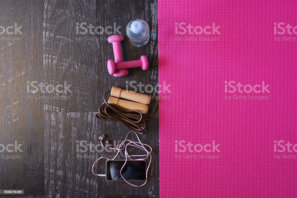 Woman fitness equipment and pink yoga mat on wooden background stock photo