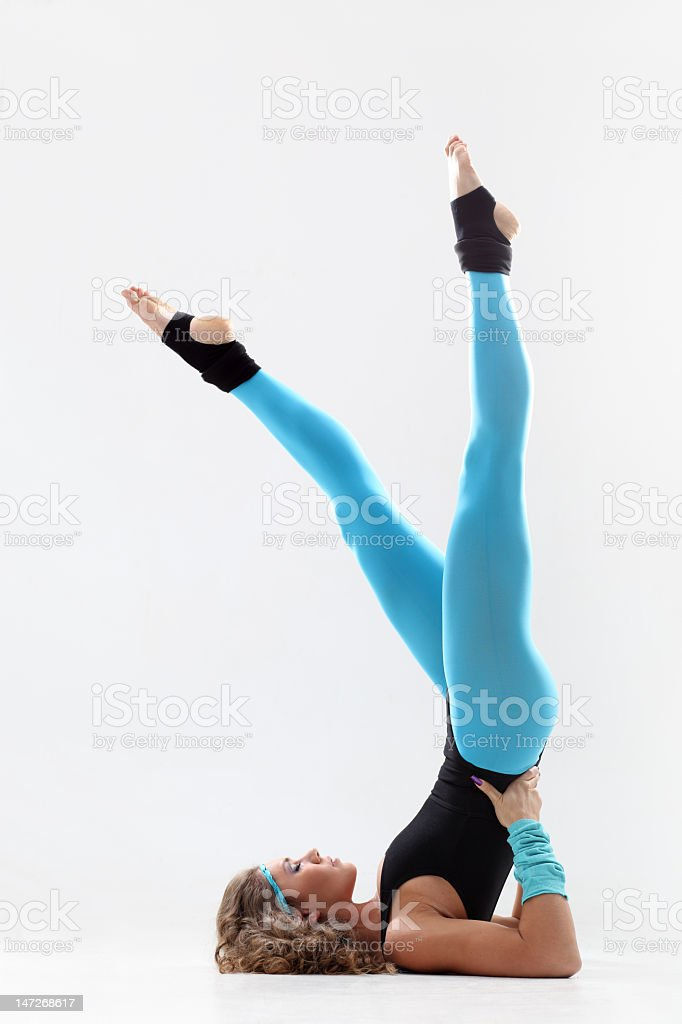 Woman fitness instructor in blue tights stretching stock photo