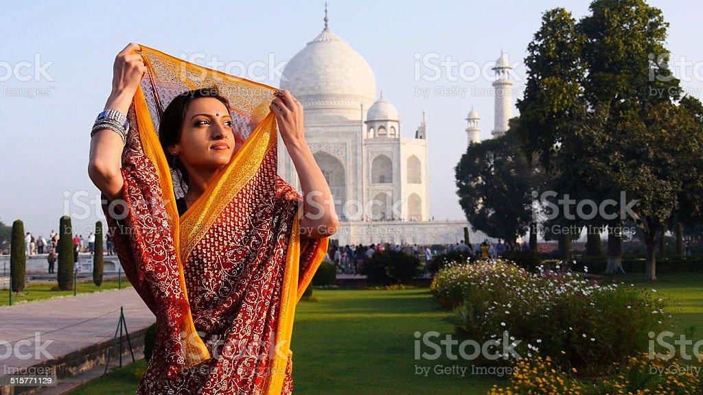 Woman fixing her sari at Taj Mahal stock photo